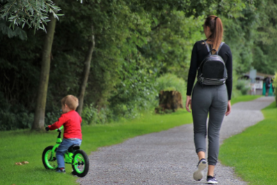 A woman walks on a trail next to her young son who is riding a bike